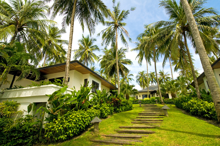 """Modern, luxury and exotic villa in the tropic island. Visible are many villas in the luxury resort, beach chairs and tables, fantastic cloudscape, many palm trees and green grass in the yard.See more images like this in:"""