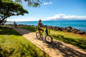Kaanapali, Hawaii, USA - December 31, 2015: Women cycling along the beach, Maui